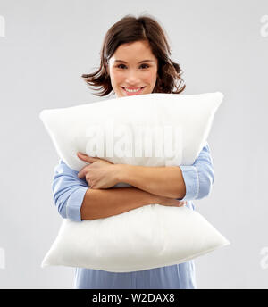 happy young woman in pajama hugging pillow - Stock Image