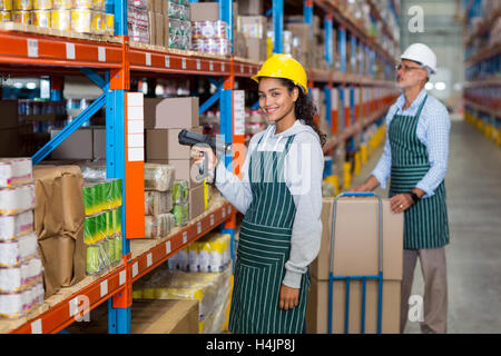 Portrait of female warehouse worker standing with barcode scanner - Stock Image