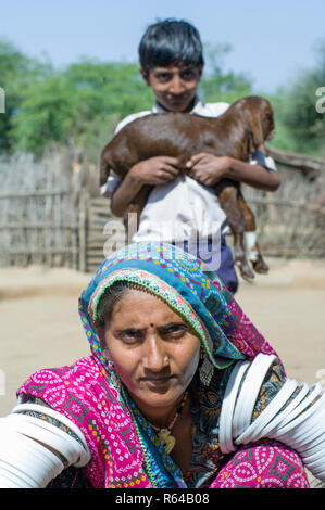 Rabari woman and boy with goat - Stock Image