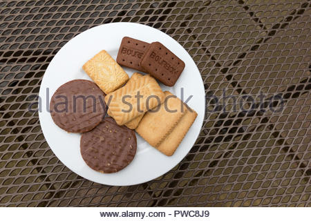 Selection of popular biscuits on a plate including custard cream and bourbon - Stock Image