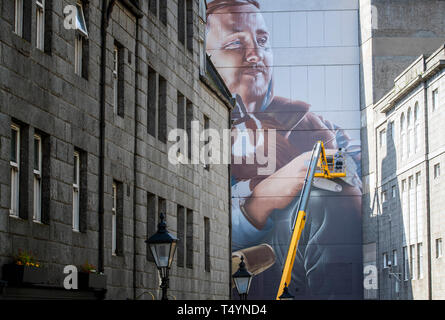 Street artist Sam Bates, aka Smug, creates a new mural for this year's Nuart Aberdeen Festival. - Stock Image