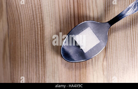 Single sugar cube lump resting on a silver metal teaspoon on a wooden textured kitchen desktop. Overhead horizontal - Stock Image