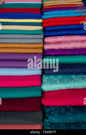 Folded sheets of colourful material lined up on display on a market stall for sale. - Stock Image