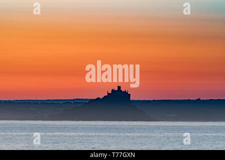 Newlyn, Cornwall, UK. 5th May 2019. UK Weather. With no wind, and a temperature of 8 degrees at sunrise, the sun rose over St Michaels Mount and the sea of Mounts Bay on bank holiday Sunday, with the promise of a fine day ahead. Credit Simon Maycock / Alamy Live News. - Stock Image