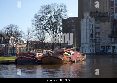 Leiden, Holland - March 24, 2019: Traditional classic boats at the Zijlsingel and the Meelfabriek building in the background - Stock Image