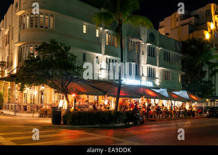 The illuminated Art Deco facade of the Cardozo hotel and sidewalk dining along Deco Drive in Miami's South Beach, - Stock Image
