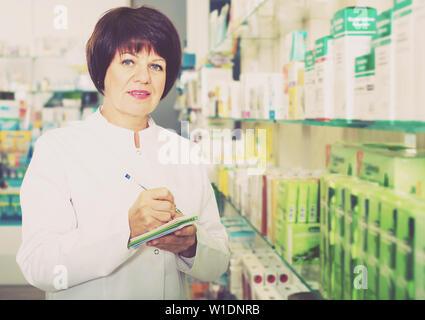 Glad woman druggist wearing white coat standing among shelves in pharmacy - Stock Image