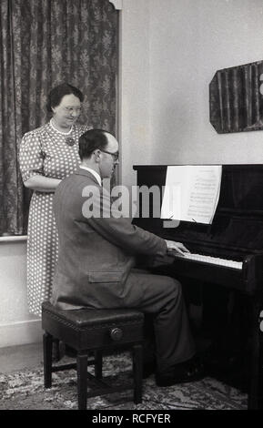 1950s, historical, at home a wife standing watching her husband play the piano, England, UK. - Stock Image