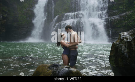 Romantic couple hugging in river under tropical waterfall - Stock Image