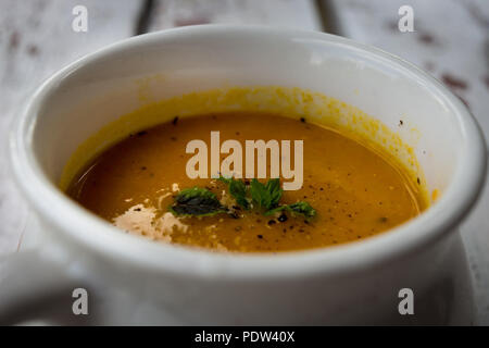 Soup with carrots, ginger and orange juice decorated with mint - Stock Image