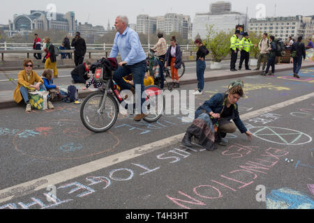 A commuter cycles past Climate Change activists with Extinction Rebellion campaigning for a better future for planet Earth after blocking Waterloo Bridge and as part of a multi-location 5-day Easter protest around the capital, on 16th April 2019, in London, England. - Stock Image