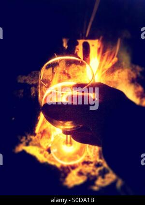 Holding wine glass near camp fire - Stock Image