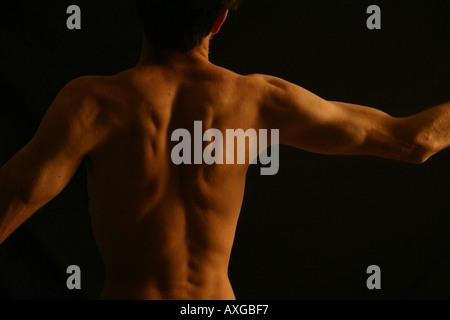 The tense shadowed back of a nude young man - Stock Image