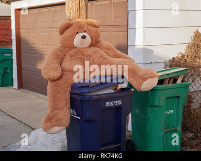 Discarded teddy bear on top of recycling bin. - Stock Image
