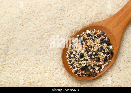 Mixed grains in a wooden spoon surrounded by rice - Stock Image