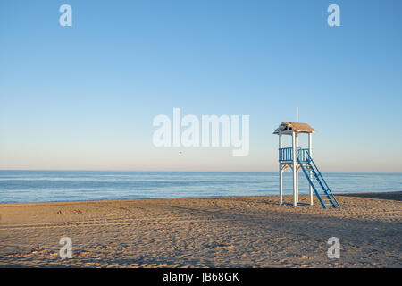 Blue and white life gaurd hut on a beach at sunset. - Stock Image