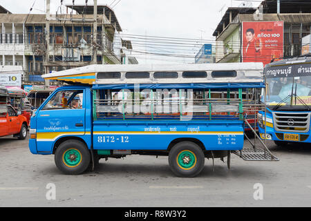 Traditional songthaew truck parked at Kanchanaburi central bus terminal, in Thailand. The vehicles are a common site in Thai cities and act as an alte - Stock Image