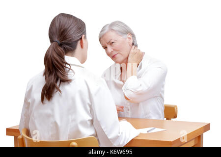 Senior female patient consulting her physician or doctor on account of acute neck pain caused by muscular tension, isolated on white background - Stock Image