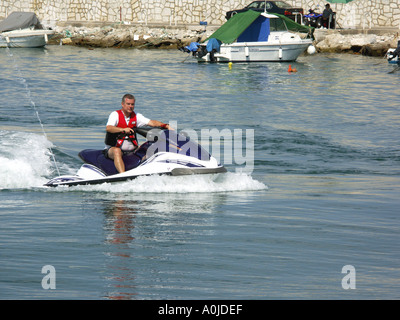 Man Riding Jet Ski ,  Fuengirola Port , Costa del Sol , Spain  men person people male adult ride riding rides EUROPE - Stock Image