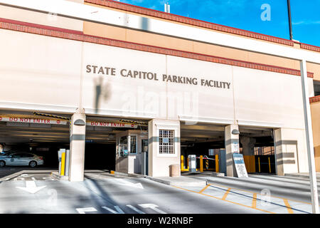 Santa Fe, USA - June 14, 2019: Capitol building in downtown center of city with parking garage entrance and sign - Stock Image