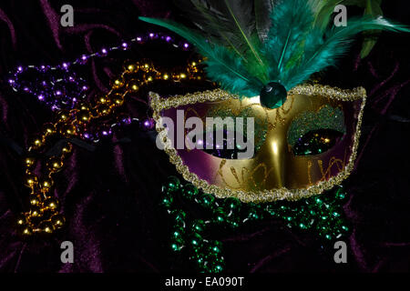 Mardi Gras mask and beads. Gold masquerade mask with green feathers, green, gold and purple beads on purple velvet - Stock Image