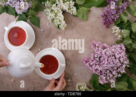 Tea set and flower decor on a textural background. Pouring tea into a mug and place under the text. View from above. Flat lay. The concept of tea drin - Stock Image