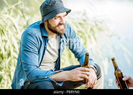Portrait of a handsome fishermen sitting with beer during the picnic on the lake at the morning - Stock Image