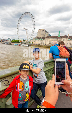 A mother takes a photograph of her young children on Westminster bridge with The London Eye in the background on a day trip to London - Stock Image