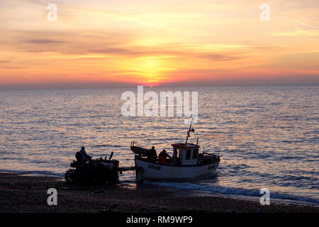 Hastings, East Sussex, UK. 14th Feb, 2019. UK Weather: Hastings fishing boat being launched at sunrise. Hastings has the largest beach-launched fishing fleet in Europe. Credit: Carolyn Clarke/Alamy Live News - Stock Image