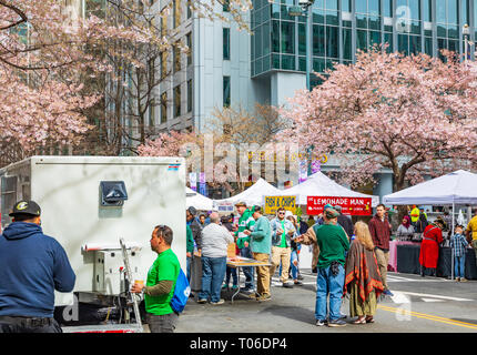 CHARLOTTE, NC, USA-3/16/19: Vendors under blossoming cherry trees draw hungry revelers on St. Patrick's day in uptown Charlotte. - Stock Image
