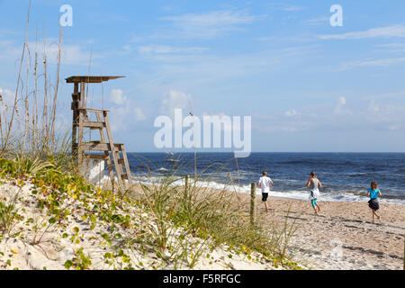 Carolina Beach, Wilmington, North Carolina. Young people running on the beach. - Stock Image
