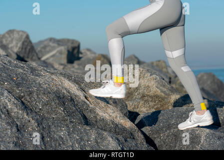 close up of a woman runners legs in leggings running across rocks - Stock Image