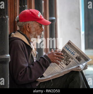 Old man reading a newspaper in Obispo, the centre of Havana, capital of the island state of Cuba - Stock Image