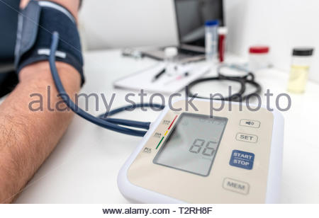 Having blood pressure read using medical device - Stock Image