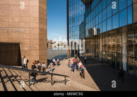 People walking along the Thames pathway outside the modern office building of 1 London Bridge, London, UK - Stock Image