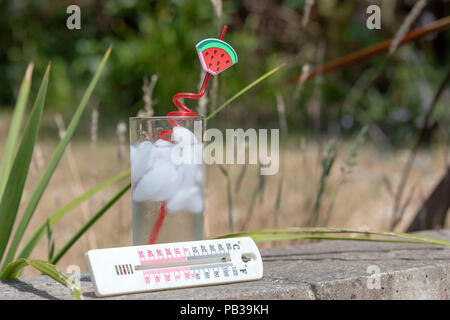 Poole, UK. 26th July 2018. A thermometer shows the hot temperature as the UK heatwave continues. Shown with a glass of iced water with a straw. Credit: Thomas Faull/Alamy Live News - Stock Image