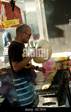 Man fanning cooking satay sticks in outdoor market - Stock Image