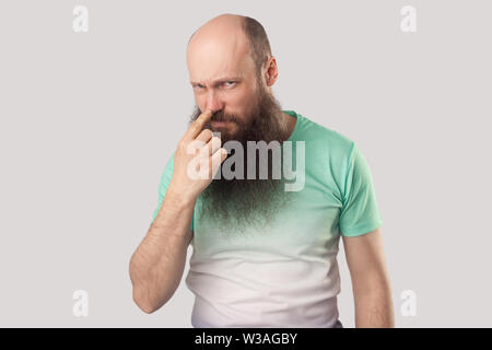 You are liar. Portrait of angry middle aged bald man with long beard in green t-shirt standing, looking and pointing at his nose, showing lie gesture. - Stock Image