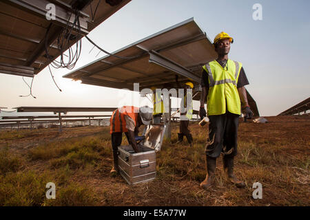 Technicians installing panels in one of East Africa's largest Solar farms, Rwamagana District, Rwanda. - Stock Image
