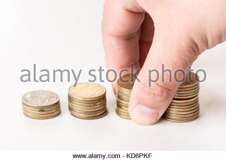 Piles of metal coins isolated above white background and hand holding pile of coins. - Stock Image
