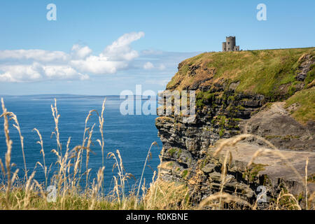 A view of O'Brien's Tower on top of the Cliffs of Moher overlooking the Atlantic ocean and Aran Islands on west coast of Ireland - Stock Image