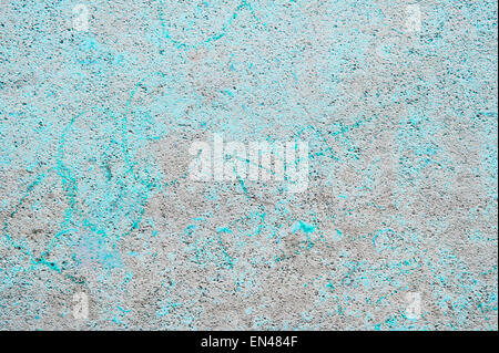A weathered stone texture with blue marks from washed off graffiti - Stock Image