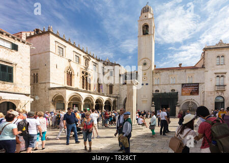 Dubrovnik, Croatia - 24th September 2017: Tourists outside the Sponza Palace and clock tower, Old Dubrovnik. The city is considering limiting the numb - Stock Image