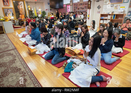 Buddhist worshippers, many from Thailand, pray & meditate at a temple  in Queens, New York City - Stock Image