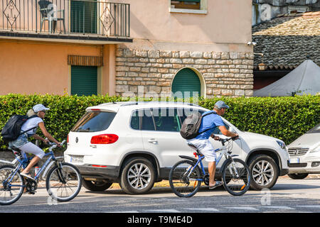 GARDA, LAKE GARDA, ITALY - SEPTEMBER 2018: Cyclists riding with traffic in the town of Garda on Lake Garda. The area is very popular for cycling - Stock Image