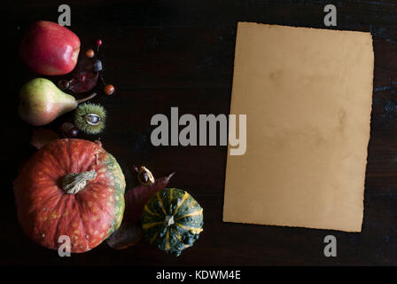 beautiful rustic fall flat lay with leaves, pumpkins, chestnuts and old vintage paper sheet  on wooden background - Stock Image