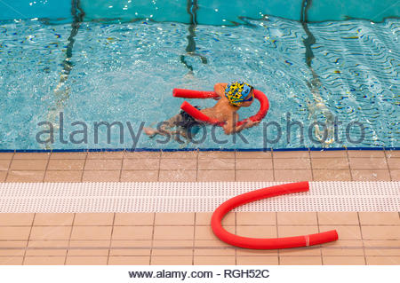 Poznan, Poland - January 26, 2019: Boy swimming with help of a red stick during lesson in the Termy Maltanskie. - Stock Image