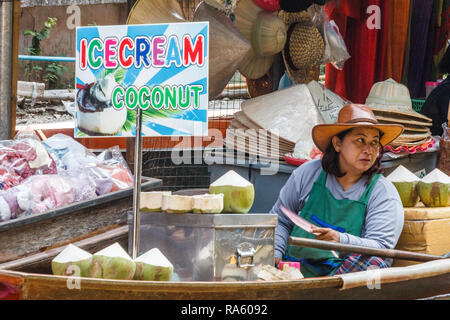 Damnoen Saduak - 4th March 2014: Women vendor selling ice cream and coconuts. The town is famous for its floating market. - Stock Image
