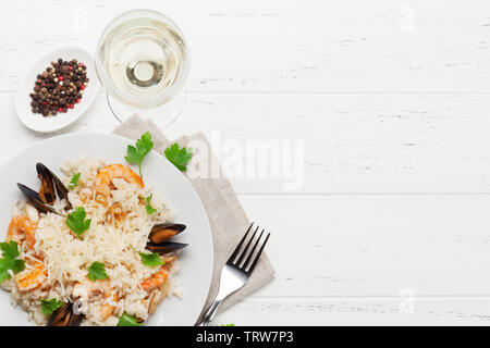 Delicious seafood risotto with shrimps, prawns, mussels. Dressed with parmesan cheese and parsley. Top view with white wine glass and copy space - Stock Image