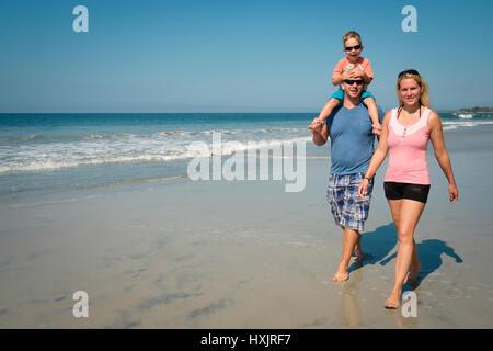 Family of 3 enjoying walk on the beach, Riviera Nayarit, Mexico - Stock Image